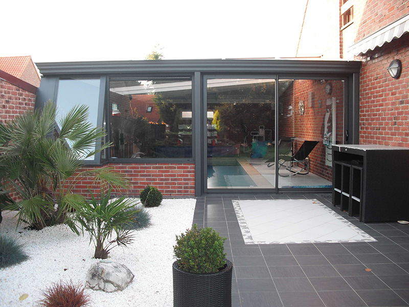 couverture de piscine de couleur gis foncé extérieur/blanc intérieur avec plantarium vitré, soubassement en briques et chéneau mouluré