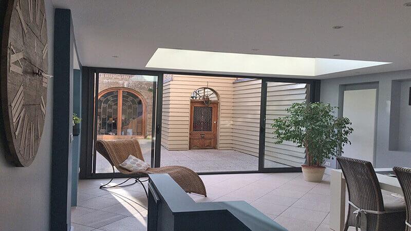 Extension d'habitation de type toiture plate de couleur gris foncé avec dôme mono-pente