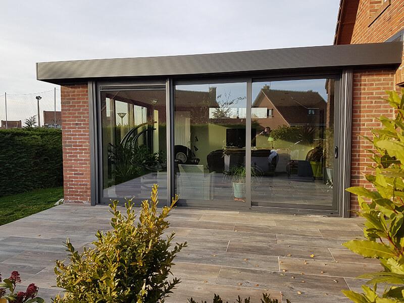 Extension d'habitation de type toiture plate de couleur gris foncé avec murs en briques  identiques à celles de la maison