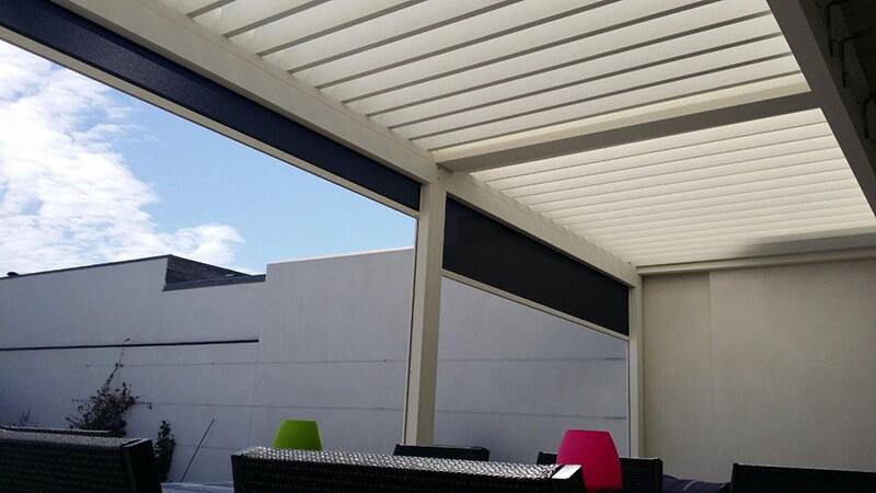 Pergola bioclimatique en aluminium à lames orientables de couleur blanche avec stores fixscreen en applique.