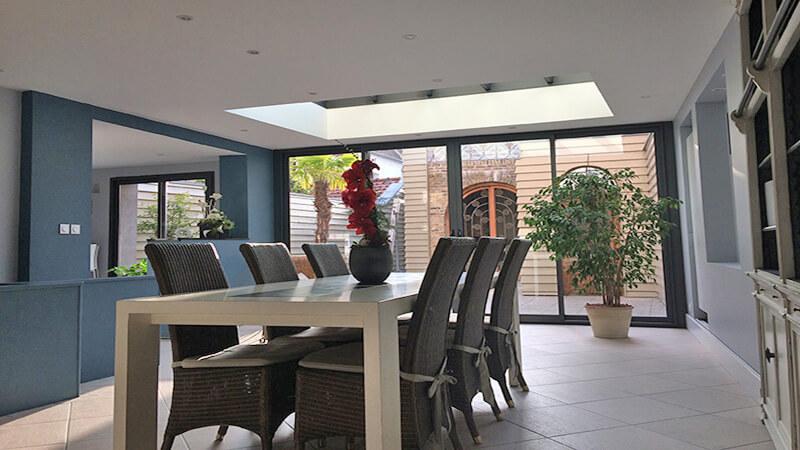 Véranda de type toiture plate de couleur taupe avec dôme mono-pente et chéneau plat contemporain après rénovation.