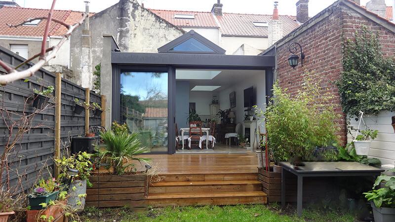 Extension d'habitation de type toiture plate de couleur gris foncé avec 3 dômes