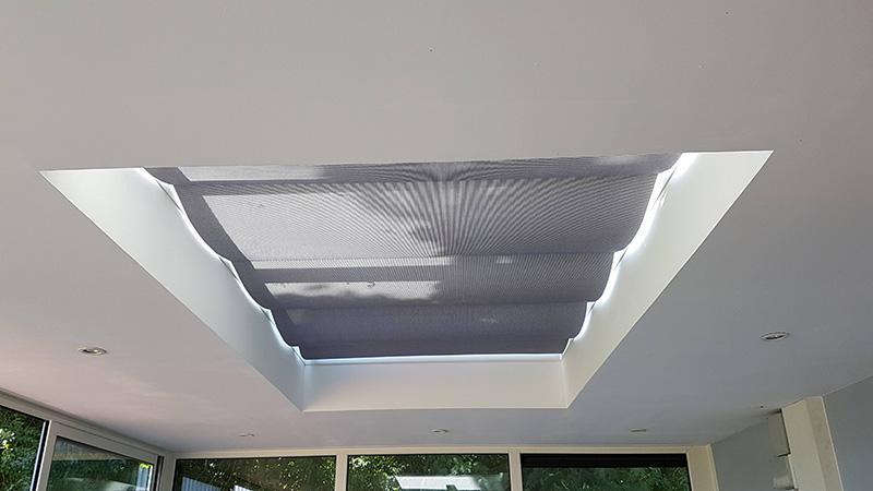 store de toiture de couleur gris clair pour puits de lumière vitré mono-pente montés sur rails coulissants