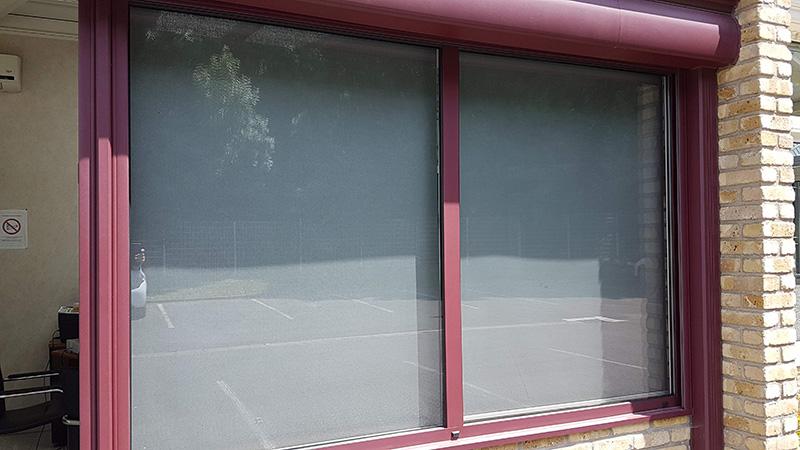 stores à enrouleur de couleur gris foncé avec coffres argentés vus de l'extérieur