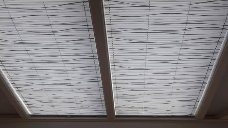 stores plissés de couleur blanc avec motifs gris pour puits de lumière vitré