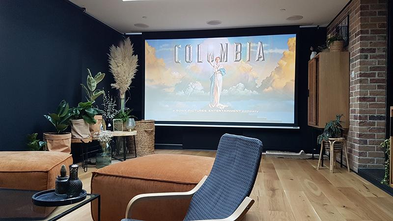 Véranda de type toiture plate de couleur noire avec dôme mono-pente, chéneau plat et traverses intermédiaires se transformant en véritable salle de cinéma.
