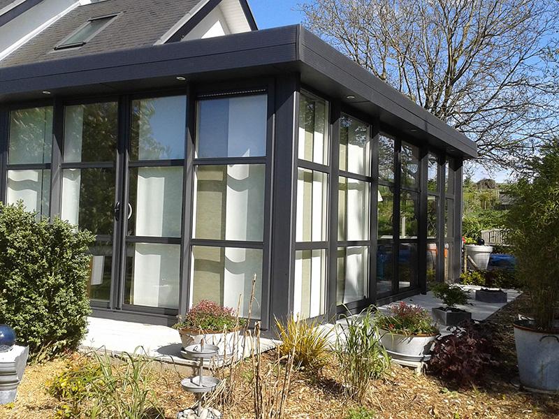 Véranda de type toiture plate de couleur gris foncé avec dôme mono-pente, traverses intermédiaires et chéneau plat