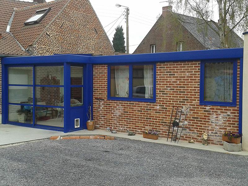 Véranda de type toiture plate de couleur bleu avec dôme mono-pente, traverses intermédiaires et chéneau plat