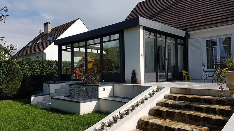 Véranda de type toiture plate de couleur gris foncé avec dôme mono-pente, chéneau plat contemporain et impostes vitrées
