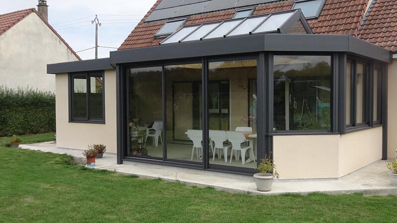 Véranda de type toiture plate de couleur gris foncé avec dôme vitré bi-pente et chéneau plat.