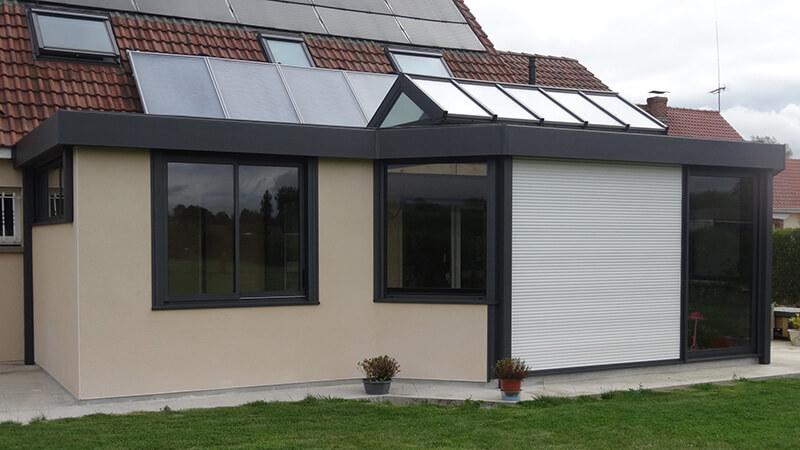 Véranda de type toiture plate de couleur gris foncé avec dôme vitré bi-pente, chéneau plat et volets roulants