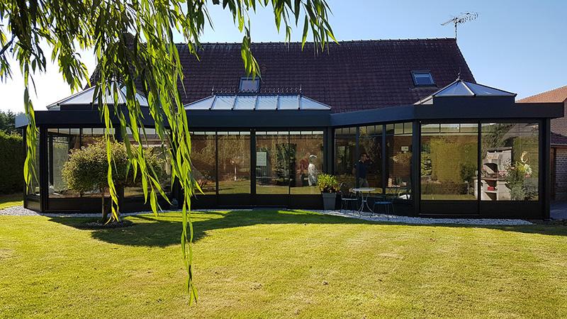 Véranda de type toiture plate de couleur noire avec 3 dômes vitrés, soubassements pleins et chéneau plat.