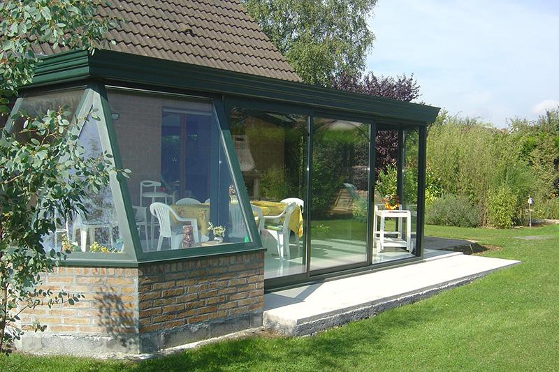 véranda de couleur vert avec 1 plantarium d'angle, chéneau mouluré et murets en briques