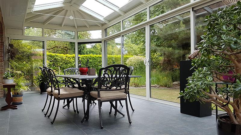 véranda victorienne 4 versants bicolore gris foncé extérieur/blanc intérieur avec impostes, pointes et crête de toiture
