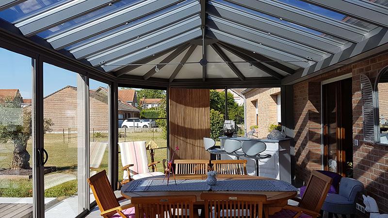 véranda victorienne 4 versants de couleur gris clair avec toiture en verre Heat Shield et panneaux sandwich blanc