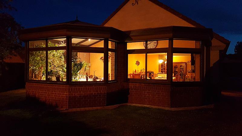 véranda victorienne de couleur taupe avec impostes vitrées et murets en briques by night