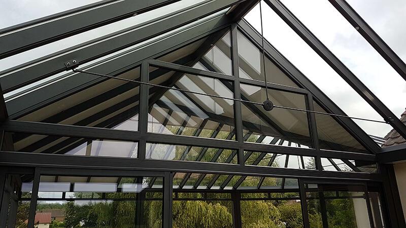véranda double pente + pergola 3 versants de couleur gris foncé sur terrasse en hauteur